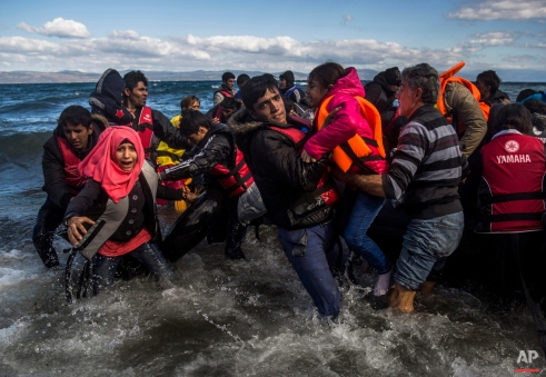 Afghan migrants disembark safely from their frail boat in bad weather on the Greek island of Lesbos after crossing the Aegean see from Turkey, Wednesday, Oct. 28, 2015. Series chronicling the migrant crisis in Europe and the influx of them coming ashore in Lesbos, Greece. More than 500,000 people have arrived in the European Union this year, seeking sanctuary or jobs and sparking the EU's biggest refugee emergency in decades. Tens of thousands of people trying to escape conflict and poverty in places like Syria and Afghanistan have been making their way across Europe this summer and fall, embarking on grueling journeys that typically start with a short boat trip from Turkey to Greece, then continue north and west on foot and by bus and train. (AP Photo/Santi Palacios)