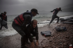 Migrants disembark from a dinghy on a beach after arriving from the Turkish coast to the village of Skala Sikaminias on the northeastern Greek island of Lesbos, on Thursday, Oct. 22, 2015. Greece is the main entry point for those fleeing violence at home and seeking a better life in the European Union. More than 500,000 people have arrived so far this year on Greece's eastern islands, paying smugglers to ferry them across from nearby Turkey. (AP Photo/Santi Palacios)