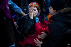 An Afghan woman holding her child reacts after arriving from Turkey at the Greek island of Lesbos, Tuesday, Oct. 27, 2015. Greece's government says it is preparing a rent-assistance program to cope with a growing number of refugees, who face the oncoming winter and mounting resistance in Europe. (AP Photo/Santi Palacios)