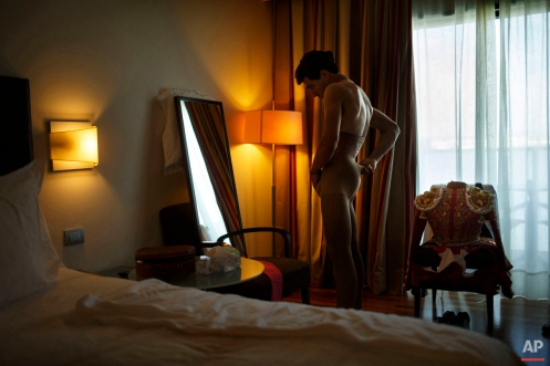 In this photo taken Saturday, May 30, 2015, Spanish bullfighter Alvaro Lorenzo adjusts his underwear while getting dressed for a bullfight with Alcurrucen ranch fighting bulls in Aranjuez, near Madrid, Spain. Bullfighters are usually dressed by their best men, and assistant named 'mozo de espadas', a ritual usually undertaken in silence and in a ceremonial manner. Bullfighting is an ancient tradition in Spain. (AP Photo/Daniel Ochoa de Olza)