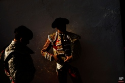 In this photo taken Saturday, May 30, 2015, Spanish bullfighter Alvaro Lorenzo's suit make golden reflections on the wall as he waits with an assistant to do the 'paseillo' or ritual entrance to the arena before a bullfight with Alcurrucen ranch fighting bulls in Aranjuez, near Madrid, Spain. Bullfighting is an ancient tradition in Spain. (AP Photo/Daniel Ochoa de Olza)