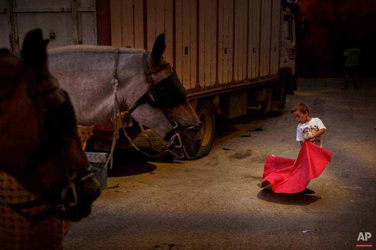 A boy plays representing the role of a bullfighter in the bullring's backstage in San Sebastian De Los Reyes, Spain, Friday, Aug. 28, 2015. Bullfighting is an ancient tradition in Spain. (AP Photo/Daniel Ochoa de Olza)