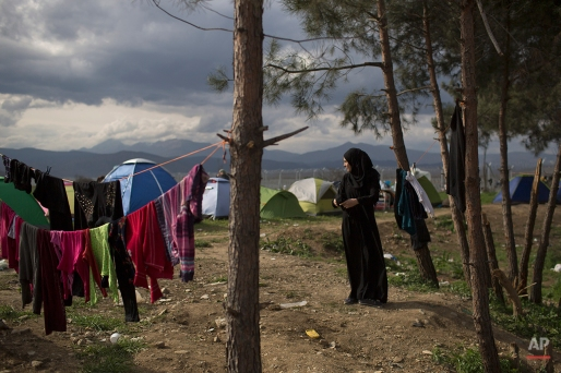 A woman hangs on clothes in a refugee camp where thousands of refugees are waiting to be allowed to cross the border into Macedonia in the northern Greek border station of Idomeni, Thursday, March 3, 2016. More than 10,000 mostly Syrian and Iraqi refugees were stuck at the country's Idomeni border crossing in deteriorating conditions. (AP Photo/Petros Giannakouris)