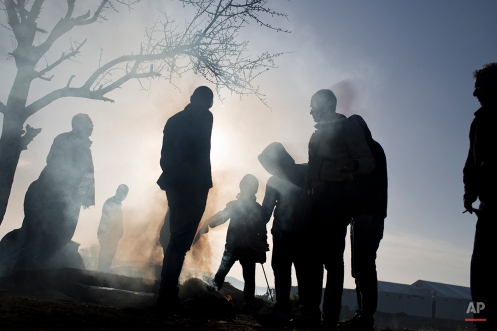 Refugees stand near a makeshift fire as they wait to be allowed to cross the border to Macedonia in the northern Greek border station of Idomeni, Wednesday, March 2, 2016. Greek police said up to 10,000 mostly Syrian and Iraqi refugees were stuck at the country's Idomeni border crossing. (AP Photo/Petros Giannakouris)