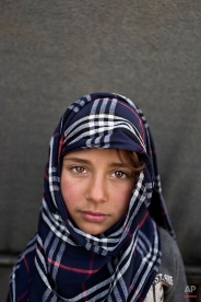 """In this Saturday, March 12, 2016 photo, Syrian refugee Hiba So'od, 6, from Hassakeh, Syria, poses for a picture at an informal tented settlement near the Syrian border on the outskirts of Mafraq, Jordan. """"I want to become a teacher,"""" says So'od. (AP Photo/Muhammed Muheisen)"""