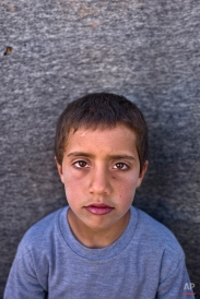 """In this Monday, March 14, 2016 photo, Syrian refugee boy Khalid Rakan, 10, from Hama, Syria, poses for a picture at an informal tented settlement near the Syrian border on the outskirts of Mafraq, Jordan. """"I just want to go back to our home in Syria"""" Khalid said. About half of the 4.8 million Syrians who fled their homeland are children, and some of the most vulnerable live in dozens of makeshift tent camps, including Jordan, which has taken in close to 640,000 refugees. Children in these camps near the northern city of Mafraq say they miss their old lives in Syria, especially going to school. (AP Photo/Muhammed Muheisen)"""