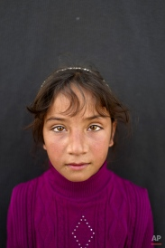 """In this Saturday, March 12, 2016 photo, Syrian refugee girl Mariam Aloush, 8, from Homs, Syria, poses for a picture at an informal tented settlement near the Syrian border on the outskirts of Mafraq, Jordan. """"I remember our home in Syria and my school there. I just want to go back,"""" says Aloush. (AP Photo/Muhammed Muheisen)"""