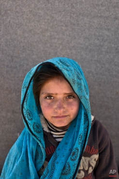 """In this Monday, March 14, 2016 photo, Syrian refugee girl Sajjida al-Hassan, 8, from Hama, Syria, poses for a picture at an informal tented settlement near the Syrian border on the outskirts of Mafraq, Jordan. """"I want to grow up and be educated"""" Sajjida said. Children in these camps near the northern city of Mafraq say they miss their old lives in Syria, especially going to school. (AP Photo/Muhammed Muheisen)"""