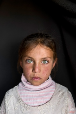 In this Sunday, March 13, 2016 photo, Syrian refugee girl Aya Bandar, 6, from Hama, Syria, poses for a picture at an informal tented settlement near the Syrian border on the outskirts of Mafraq, Jordan. About half of the 4.8 million Syrians who fled their homeland are children, and some of the most vulnerable live in dozens of makeshift tent camps, including in Jordan, which has taken in close to 640,000 refugees. (AP Photo/Muhammed Muheisen)