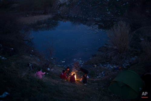 Refugees warm themselves up near a makeshift fire as they wait to be allowed to cross the border to Macedonia in the northern Greek border station of Idomeni, Wednesday, March 2, 2016. Greek police said up to 10,000 mostly Syrian and Iraqi refugees were stuck at the country's Idomeni border crossing in deteriorating conditions. (AP Photo/Petros Giannakouris)