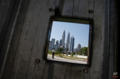 A security guard patrols at a construction site in front of Petronas Twin Towers, center, in Kuala Lumpur, Malaysia, Wednesday, March 2, 2016. The Petronas Twin Towers is one of the major landmarks in Kuala Lumpur city center alongside Kuala Lumpur Tower. (AP Photo/Joshua Paul)