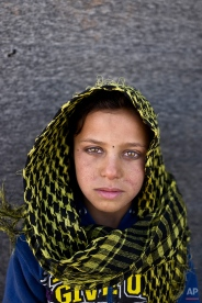 """In this Monday, March 14, 2016 photo, Syrian refugee girl Mayada Hammid, 8, from Hassakeh, Syria, poses for a picture at an informal tented settlement near the Syrian border on the outskirts of Mafraq, Jordan. """"I remember nothing from Syria,"""" says Hammid. (AP Photo/Muhammed Muheisen)"""