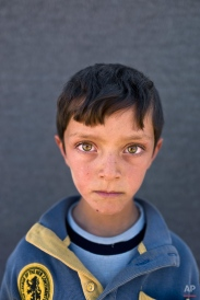 """In this Friday, March 11, 2016 photo, Syrian refugee boy Ahmad Zughayar, 6, from Deir el-Zour, Syria, poses for a picture at an informal tented settlement near the Syrian border on the outskirts of Mafraq, Jordan. """"I remember the sound of bombings on homes in Deir el-Zour,"""" says Zughayar. (AP Photo/Muhammed Muheisen)"""