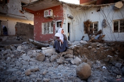 A woman looks at her ruined house in Cizre, Turkey, early Wednesday, March 2, 2016. Turkish authorities on Wednesday scaled down a 24-hour curfew imposed on the mainly Kurdish town of Cizre in southeast Turkey, nearly three weeks after declaring the successful conclusion of military operations there. The curfew was lifted at 5 a.m., allowing residents to return to their conflict-stricken neighborhoods for the first time since Dec. 14. But it will remain in effect between 7:30 p.m. and 5 a.m. Residents began trickling back at first light, their vehicles loaded with personal belongings and, in some cases, children. (AP Photo/Emrah Gurel)