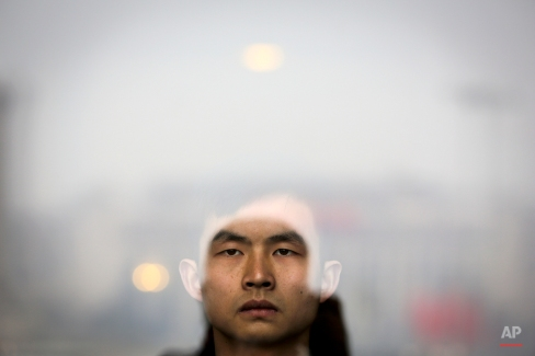 A soldier dressed as an usher stands guard at an entrance door of the Great Hall of the People, where the opening session of the Chinese People's Political Consultative Conference (CPPCC) is held, in Beijing, Thursday, March 3, 2016. The more than 2,000 members of China's top legislative advisory body convened their annual meeting Thursday, kicking off a political high season that will continue with the opening of the national congress on Saturday. (AP Photo/Andy Wong)