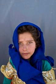 """In this Monday, March 14, 2016 photo, Syrian refugee girl Zahra al-Jassim, 10, from Hama, Syria, poses for a picture at an informal tented settlement near the Syrian border on the outskirts of Mafraq, Jordan. """"I dream of going back to Syria to see my friends Raghd, Halima, and Najwa,"""" says al-Jassim. (AP Photo/Muhammed Muheisen)"""