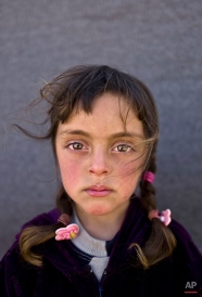 In this Friday, March 11, 2016 photo, Syrian refugee girl Zahra Mahmoud, 5, from Deir el-Zour, Syria, poses for a picture at an informal tented settlement near the Syrian border on the outskirts of Mafraq, Jordan. About half of the 4.8 million Syrians who fled their homeland are children, and some of the most vulnerable live in dozens of makeshift tent camps, including in Jordan, which has taken in close to 640,000 refugees. (AP Photo/Muhammed Muheisen)