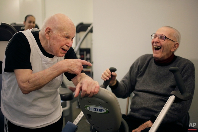 In this Thursday, March 24, 2016 photo, 100-year-old Samuel Bender, left, laughs with 87-year-old Richard Forsyth, right, while working out in a gym at Laurelmead Cooperative retirement community, in Providence, R.I. The wealthy retirement community has six centenarians. (AP Photo/Steven Senne)