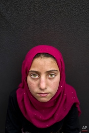 """In this Sunday, March 13, 2016 photo, Syrian refugee girl Yasmeen Mohammed, 11, from Eastern Ghouta, Syria, poses for a picture at an informal tented settlement near the Syrian border on the outskirts of Mafraq, Jordan. Mohammed, whose family fled their town, said she misses her old life. """"All I want is to go back to my school in Syria and see my friends,"""" she said. (AP Photo/Muhammed Muheisen)"""