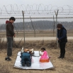 South Korean children Park Yeon-hee and Park Yeon-jung, center right, bow to pay to respect for their ancestors in North Korea, in front of the barbed wire fence as they celebrate the Lunar New Year at the Imjingak Pavilion, near the demilitarized zone of Panmunjom, in Paju, South Korea, Monday, Feb. 8, 2016. Millions of South Koreans visit their hometowns during the four-day holiday that began Sunday. (AP Photo/Ahn Young-joon)