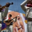 In this Feb. 14, 2016 photo, Mariachis play in front of street art depicting Pope Francis, as they wait for the popemobile to pass after Mass in Ecatepec, Mexico. Pope Francis urged Mexicans to shun the devil and resist the temptations of wealth and corruption as he celebrated an open-air Mass for hundreds of thousands of people. (AP Photo/Rebecca Blackwell)