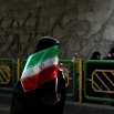 An Iranian woman holds the national flag during a rally commemorating the 37th anniversary of the Islamic revolution, in Tehran, Iran on Thursday, Feb. 11, 2016. The nationwide rallies commemorate Feb. 11, 1979, when followers of Ayatollah Khomeini ousted U.S.-backed Shah Mohammad Reza Pahlavi. (AP Photo/Ebrahim Noroozi)