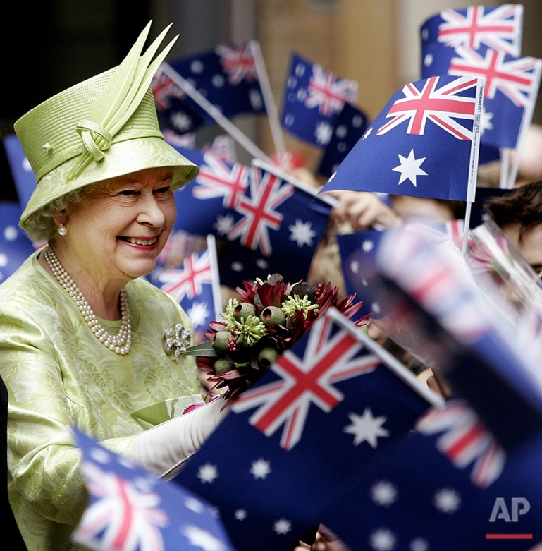 Britain's Queen Elizabeth ll,  left, receives flowers from waiting school children with waiving national flags after the Commonwealth Day Service in Sydney,  Monday, March 13, 2006. The Queen will open the Melbourne Commonwealth Games on March 15, 2006. (AP Photo/Rob Griffith, Pool)