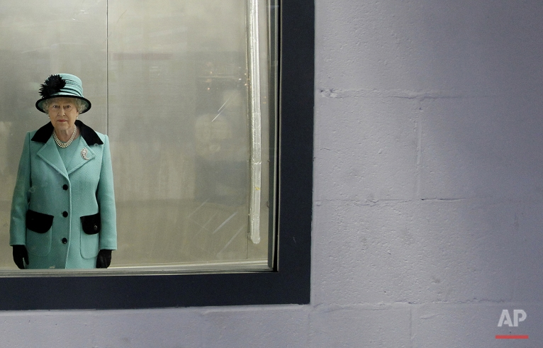 Britain's Queen Elizabeth II looks through a window, during a visit to the new Coca Cola factory, which she officially opened, in Lisburn, Northern Ireland, Friday, Oct. 22, 2010. (AP Photo/Peter Morrison)