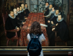 A visitor views The Somerset House Conference painting at the exhibition of English portraits in the Tretyakov Gallery in Moscow, Russia, Thursday, April 21, 2016. The exhibition from the collection of the National Portrait Gallery in London opened at the gallery and includes major British works. (AP Photo/Alexander Zemlianichenko)