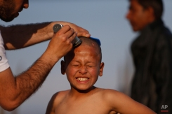 A migrant boy has a haircut in a makeshift camp at the border crossing at the northern Greek border point of Idomeni, Greece, Wednesday, April 6, 2016. Stranded migrants are spending their days in a makeshift camp near the railway station and waiting for borders to be opened. (AP Photo/Amel Emric)