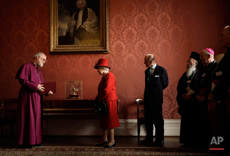 Britain's Queen Elizabeth II, second left, is shown the Ampulla and Coronation Spoon used at her coronation in 1953 by the Archbishop of Canterbury Rowan Williams, left, as her husband Prince Philip, third from left, and other Christian guests watch as they attend a multi-faith reception to mark the Diamond Jubilee of the Queen's Accession at Lambeth Palace in London, Wednesday, Feb. 15, 2012. (AP Photo/Matt Dunham)