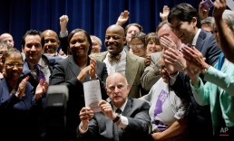 California Gov. Jerry Brown holds a signed bill creating the highest statewide minimum wage at $15 an hour by 2022 at the Ronald Reagan State Building in Los Angeles, Monday, April 4, 2016. (AP Photo/Damian Dovarganes)