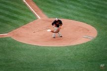 A groundskeeper tosses dirt around home plate before an opening day baseball game between the Baltimore Orioles and the Minnesota Twins in Baltimore, Monday, April 4, 2016. (AP Photo/Patrick Semansky)