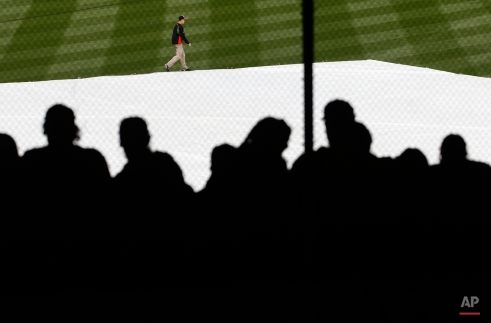 Fans sit in the stands as a groundskeeper walks past a tarp covering the infield during a rain delay before an opening day baseball game between the Baltimore Orioles and the Minnesota Twins in Baltimore, Monday, April 4, 2016. (AP Photo/Patrick Semansky)