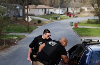 In this March 9, 2016 photo, Atlanta police officers Michael Costello, left, and Jacob Fletcher walk into a neighborhood looking for clues an unsolved murder as part of a Tactical Neighborhood Canvass in Atlanta. Costello is the first officer to be part of the Atlanta Police Foundation's Secure Neighborhoods initiative. The new program helps Atlanta police officers achieve the dream of home ownership while at the same time aiming to increase police visibility and improve engagement between officers and the community. (AP Photo/David Goldman)