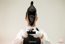 A Christie's employee holds 'The Mendes-France Baule Mask' from Ivory Coast at Christies's auction rooms in London, Monday, April 11, 2016. The mask is estimated to realise 500,000-800,000 US dollars (355,537-568,858 UK pounds) when it is auctioned in New York in the Post War and Contemporary Afternoon sale on May 11. (AP Photo/Kirsty Wigglesworth)