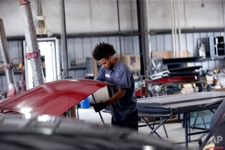 In this March 29, 2016 photo, Montrel Stiebling, a former inmate at the Louisiana State Penitentiary in Angola and graduate of their work release training program, works on a car in the body shop of Toyota of New Orleans in New Orleans. Judges have hand-picked dozens of non-violent offenders to spend at least two years at Angola, avoiding much longer prison sentences. The judges see evidence that the program is breaking a cycle of crime for its graduates. And they say the prison's mentors deserve much of the credit. (AP Photo/Gerald Herbert)