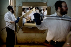 Jewish Orthodox bakers make matza, a traditional handmade Passover unleavened bread, at a Tzanz Hasidic dynasty community bakery in Netanya, Israel, Wednesday, April 13, 2016. Jews are forbidden to eat leavened foodstuffs during the Passover Holiday. Passover celebrates the biblical story of the Israelites' escape from slavery and exodus from Egypt. (AP Photo/Ariel Schalit)