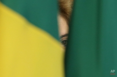 Brazil's President Dilma Rousseff is barely seen between two Brazilian flags during a meeting at the Planalto Presidential Palace, in Brasilia, Brazil, Wednesday, April 13, 2016. President Rousseff is facing impeachment proceedings that stem from allegations her administration violated fiscal rules to mask budget problems by shifting around government accounts. (AP Photo/Eraldo Peres)