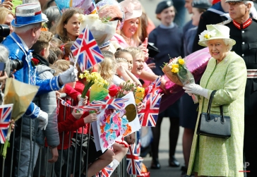 Britain's Queen Elizabeth II collects flowers and good wishes during a walkabout to celebrates her 90th birthday in Windsor, England, Thursday, April, 21, 2016. (AP Photo/Alastair Grant)