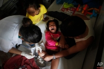 In this July 24, 2015 photo, Khendo Tamang, 8, in yellow, stands by the bedside of her best friend Nirmala Pariyar, also 8, as she cries in pain during treatment on her amputated right leg in the Bir Trauma Center in Kathmandu, Nepal. Losing a leg each in the massive Nepal earthquake in 2015, they were both taken to Bir Hospital and Kathmandu's main trauma ward where they spent the next three months with surgeries and physical therapy with their new prostheses. During this time the girls' friendship grew and have become inseparable. (AP Photo/Niranjan Shrestha)