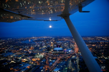 A near full moon hangs over the city of New Orleans at dusk in this aerial photo, Thursday, April 21, 2016. (AP Photo/Gerald Herbert)