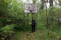 A man stands under a basketball board near a facility for refugees in Principovac, about 100 km west from Belgrade, Serbia, Friday, April 8, 2016. Migrants stuck on the Serbian side of the frontier since early March when Balkan countries abruptly shut their borders to migrants wanting to reach Germany and other seemingly wealthy Western European countries. (AP Photo/Darko Vojinovic)