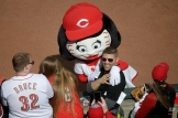 Cincinnati Reds mascot Rosie Red poses for a photograph with a fan before their opening day baseball game against the Philadelphia Phillies, Monday, April 4, 2016, in Cincinnati. (AP Photo/John Minchillo)