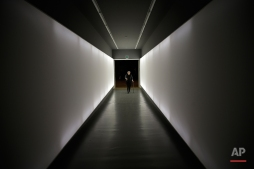 An elderly visitor walks in a corridor of the Triennale museum during the Design Fair exhibition, in Milan, Italy, Monday, April 11, 2016. (AP Photo/Luca Bruno)
