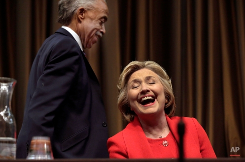 Democratic presidential candidate Hillary Clinton laughs as the Rev. Al Sharpton walks to the podium at the 25th annual National Action Network convention in New York, Wednesday, April 13, 2016. (AP Photo/Richard Drew)