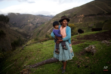 Teofila Wachaca holds her two-year-old son Ronaldinio, while working on their farm in Uchuraccay, Peru, Friday, April 8, 2016. Peruvians head to the ballot box Sunday. Polls show Keiko Fujimori as the favorite going into Sunday's presidential contest, with a double-digit lead, although she is expected to fall short of capturing the simple majority of votes needed to avoid a June runoff. (AP Photo/Rodrigo Abd)