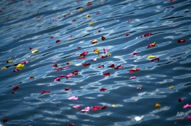 Flower petals rest on the surface of the Manzanares river during an event marking the International Roma Day in Madrid, Friday, April 8, 2016. Members of the Spain's gypsy community threw flower petals into the river during a ceremony symbolizing the departure of their ancestors from India and their exodus across the world. (AP Photo/Francisco Seco)