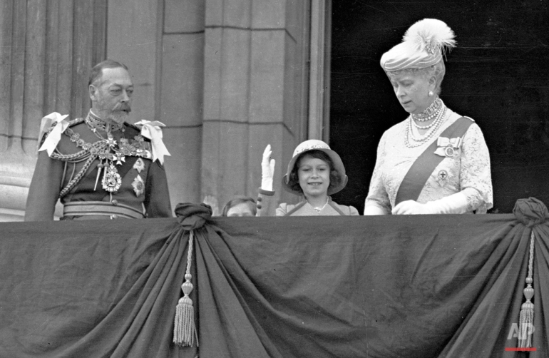 Britain's Queen Elizabeth II, then Princess Elizabeth, centre, waves as she stands on the on the balcony of Buckingham Palace, London, with her grandparents King George V and Queen Mary, in this May 6, 1935 photo. Princess Margaret is just visible over the balcony edge.   (AP Photo)