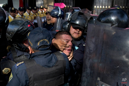 Police detain a taxi driver who, along with other cabbies, blocked a main road to protest the one day per week driving restriction in Mexico City, Wednesday, April 13, 2016. Last week, under new regulations imposed after the capital experienced its worst air-quality crisis in over a decade, 40 percent of cars were ordered temporarily off the road. The anti-pollution measures run through the end of June, when the rainy season begins. (AP Photo/Eduardo Verdugo)